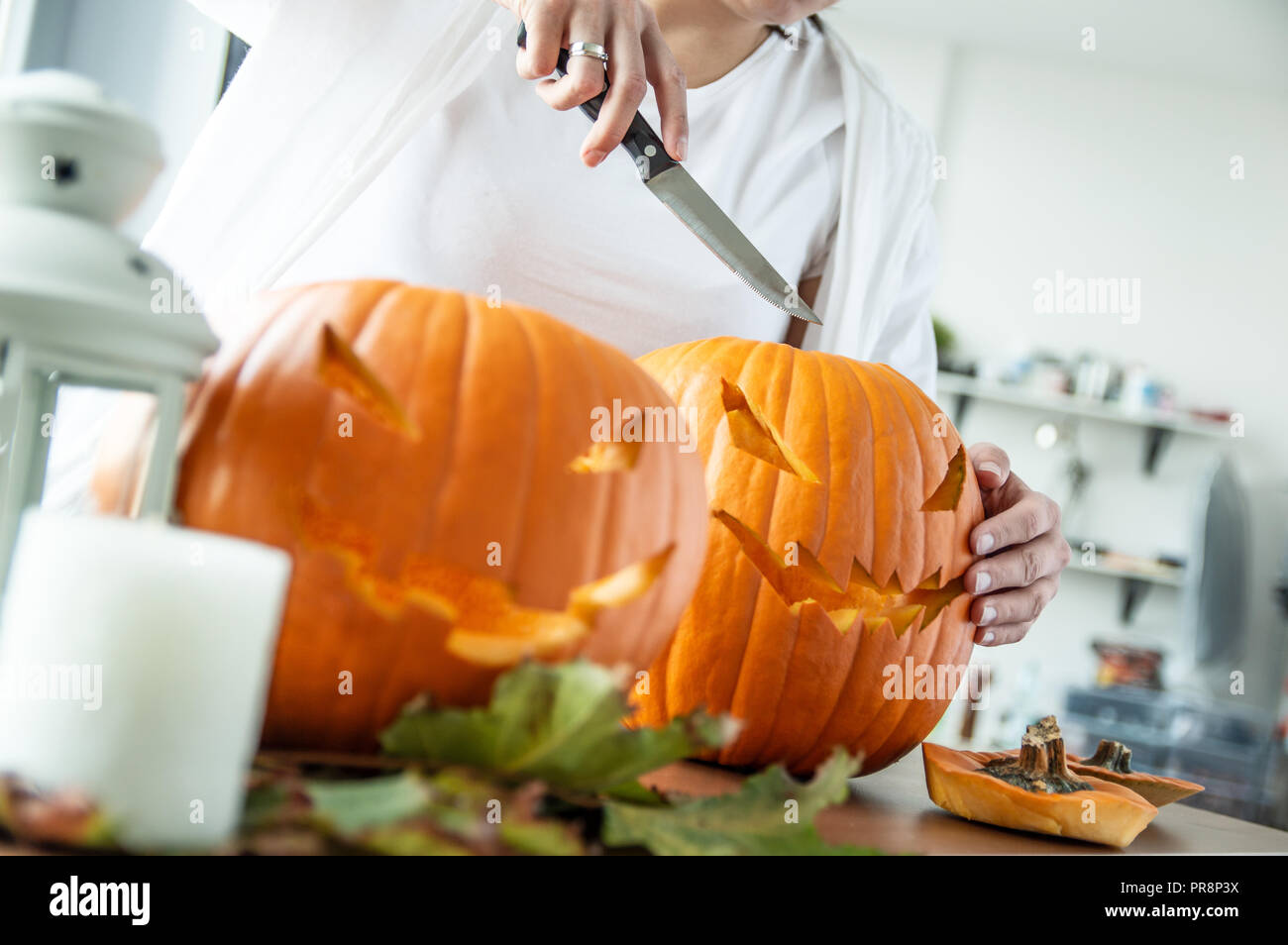 Woman's hand with knife cuts pumpkin for Halloween. Horizontal orientation - Stock Image