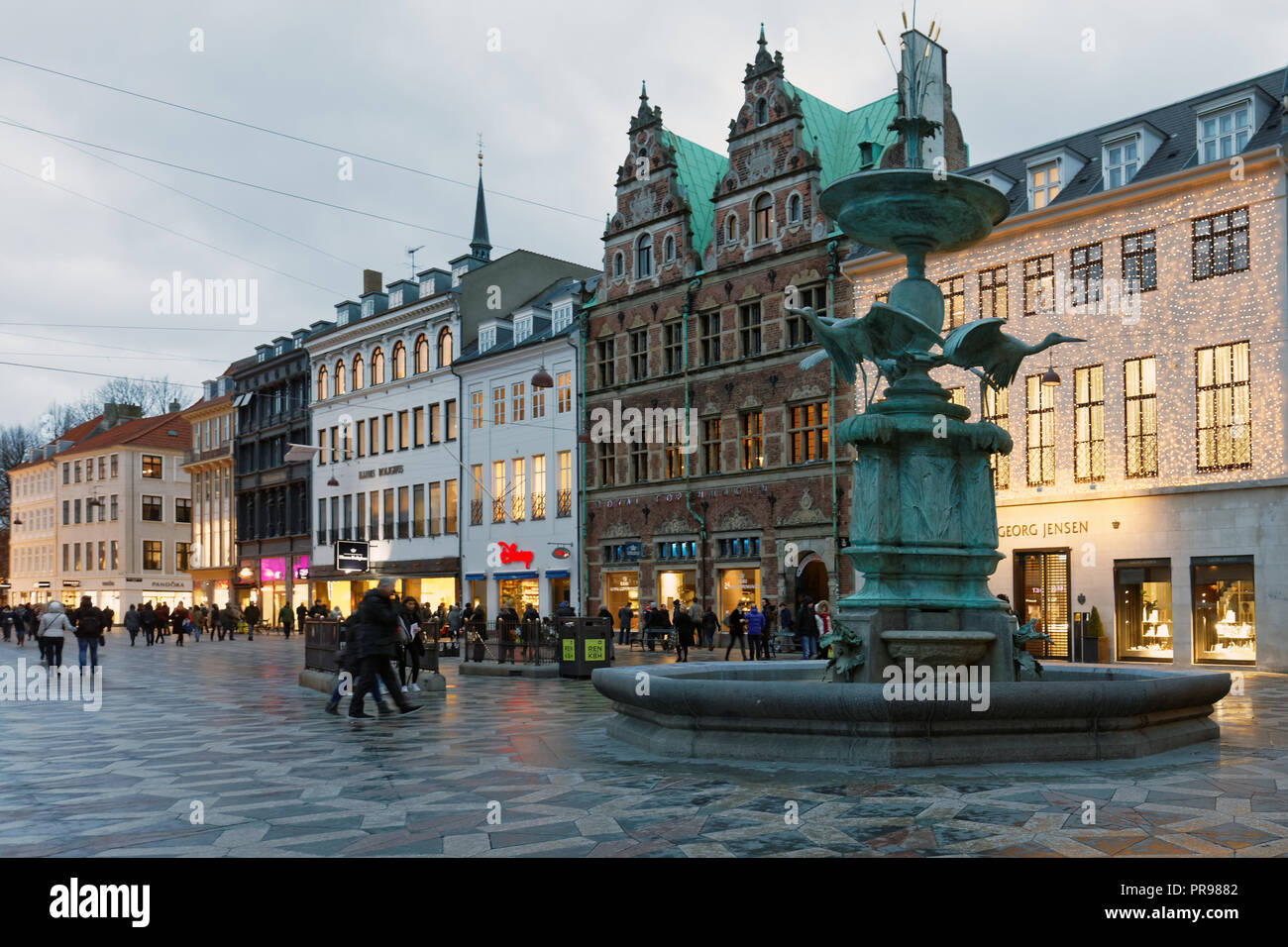 Copenhagen, Denmark - November 6, 2016: People walking at the Stork Fountain on Amagertorv square. The fountain erected in 1894 by design of  Edvard P - Stock Image