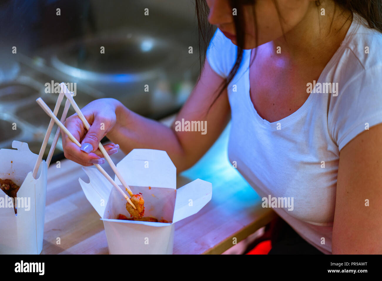 Close up of young attractive woman eating asian food with chopsticks at cafe. - Stock Image