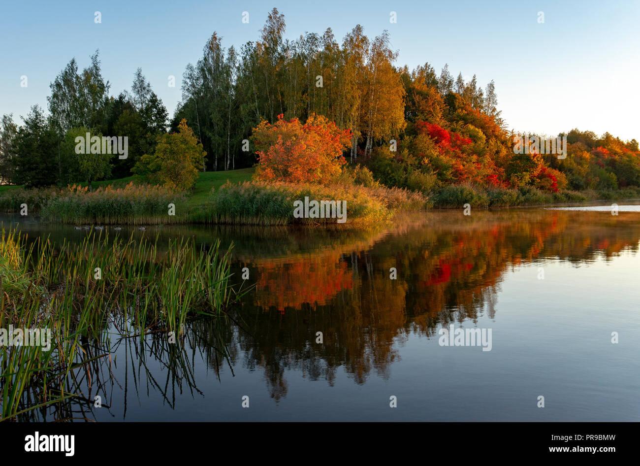 Fall season start idyllic lake reflections of fall foliage. Colorful autumn foliage casts its reflection on the calm waters - Stock Image