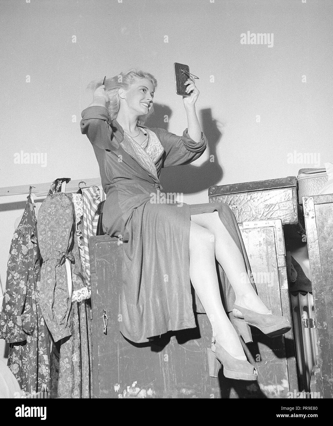 Woman fixing her hair in the 1940s. A young blonde woman is looking at herself in a pocket mirror while combing her hair. Sweden 1940s. Photo Kristoffersson ref X30-1 - Stock Image