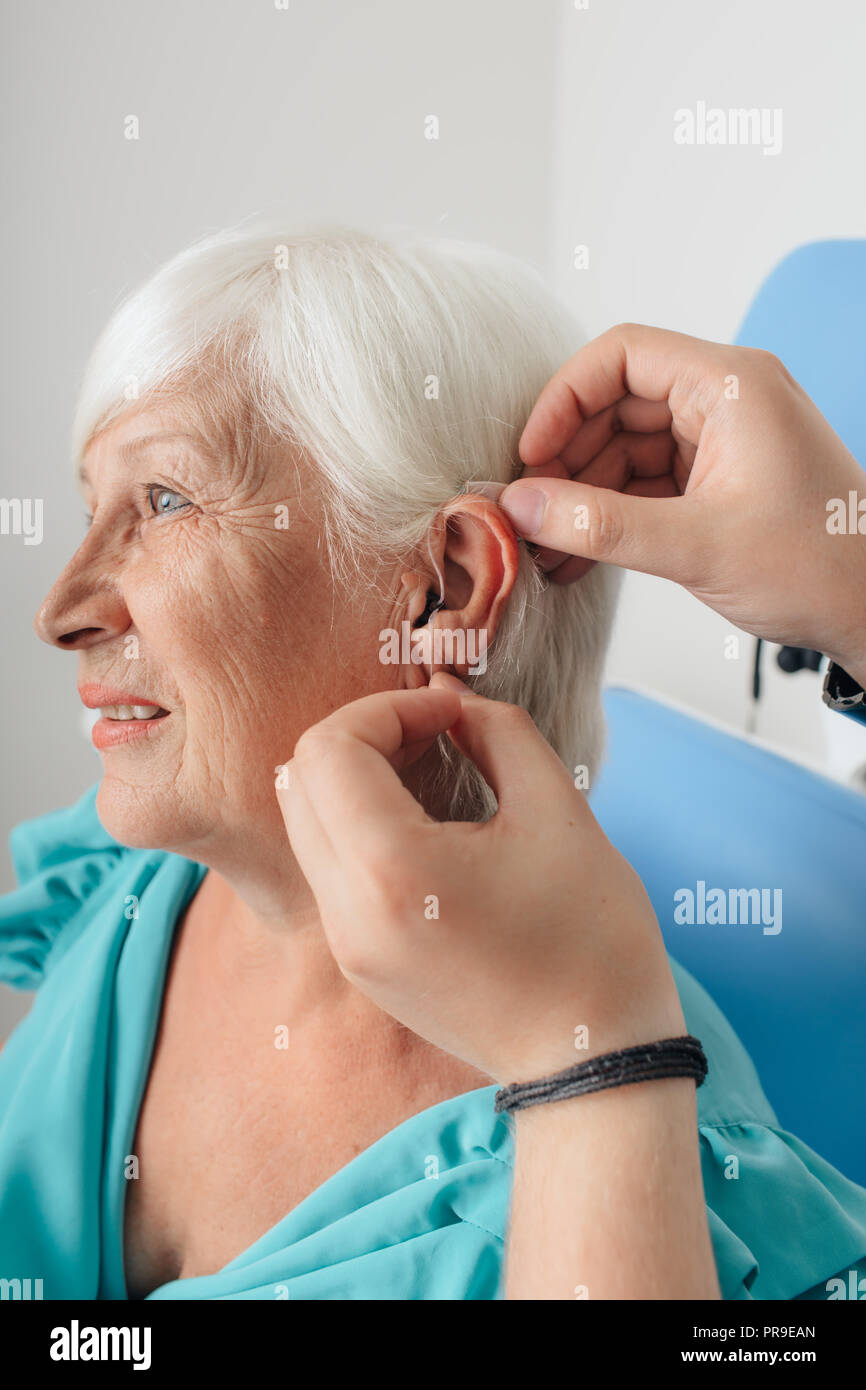 Cropped doctor's hand applying hearing aid for an aged woman - Stock Image
