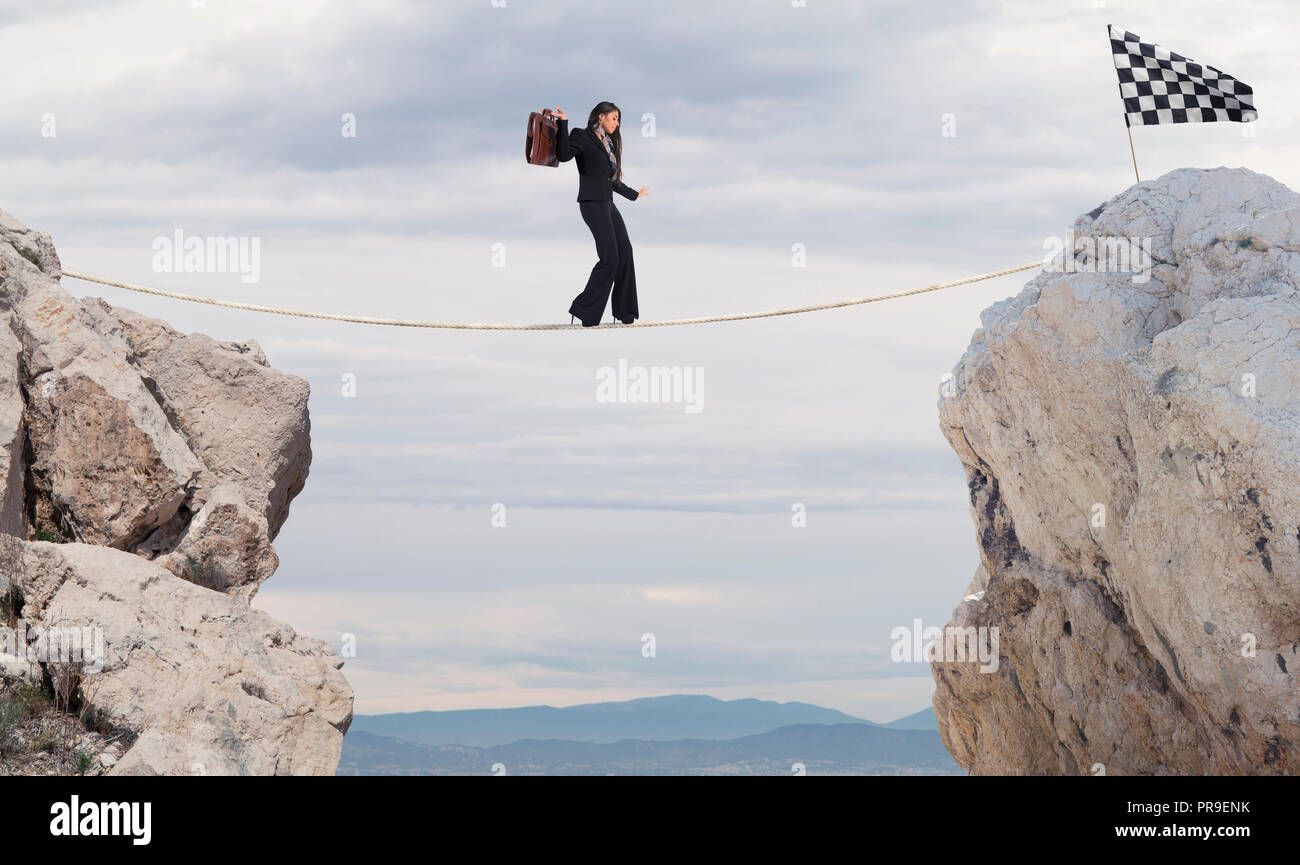Business concept of businesswoman who overcome the problems reaching the flag on a rope - Stock Image