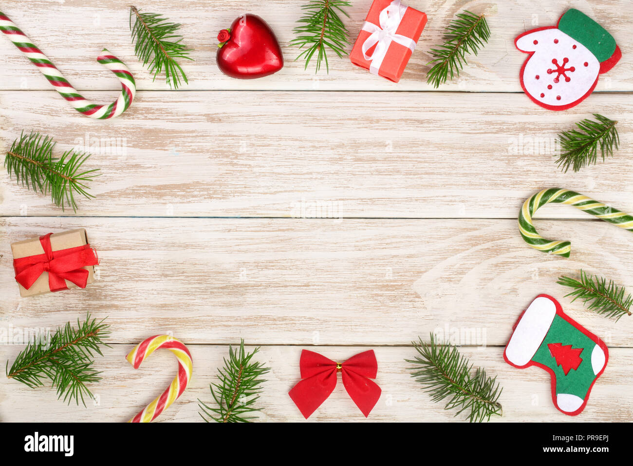 Christmas frame made of fir branches decorated with candy canes and boxes on a light wooden background Stock Photo