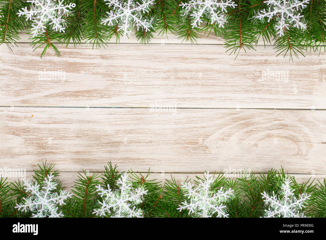 Christmas frame made of fir branches decorated with snowflakes on a light wooden background - Stock Image