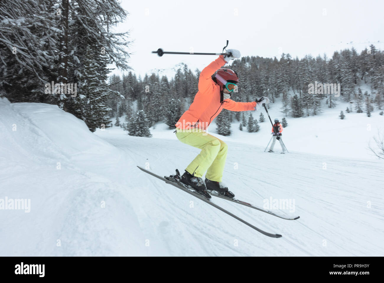 Young woman, girl in orange, green, yellow ski suit jumping in the forest - Stock Image