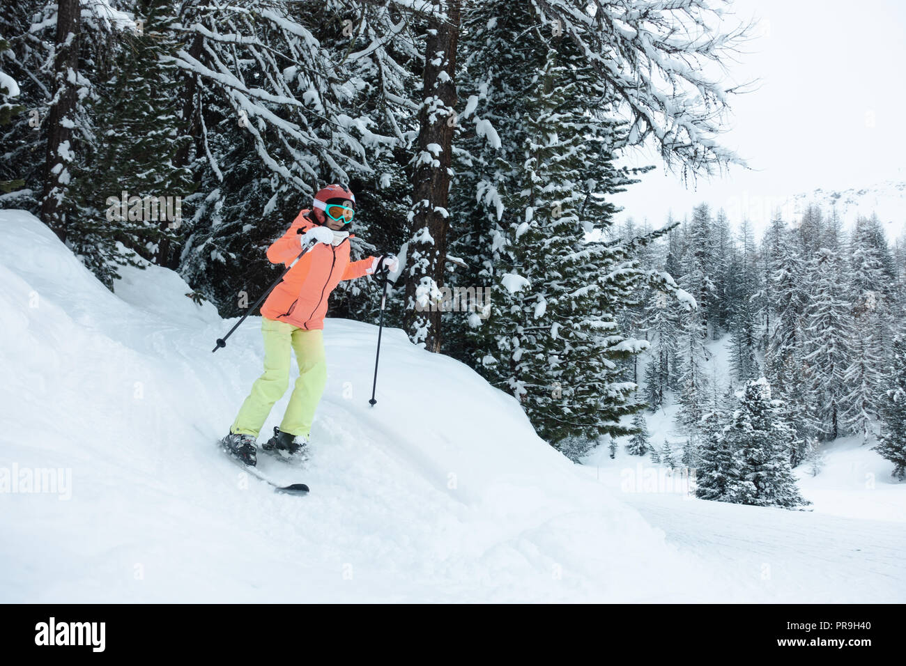 Young woman, girl in orange, green, yellow ski suit skiing in the forest - Stock Image