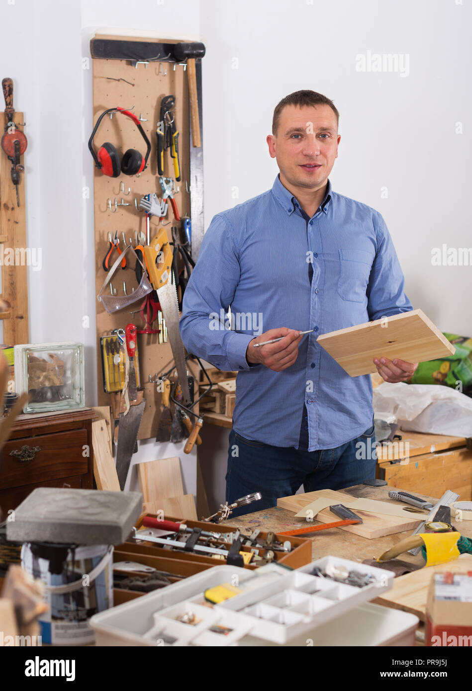 Smiling adult woodworker working with  wood plank at workplace - Stock Image