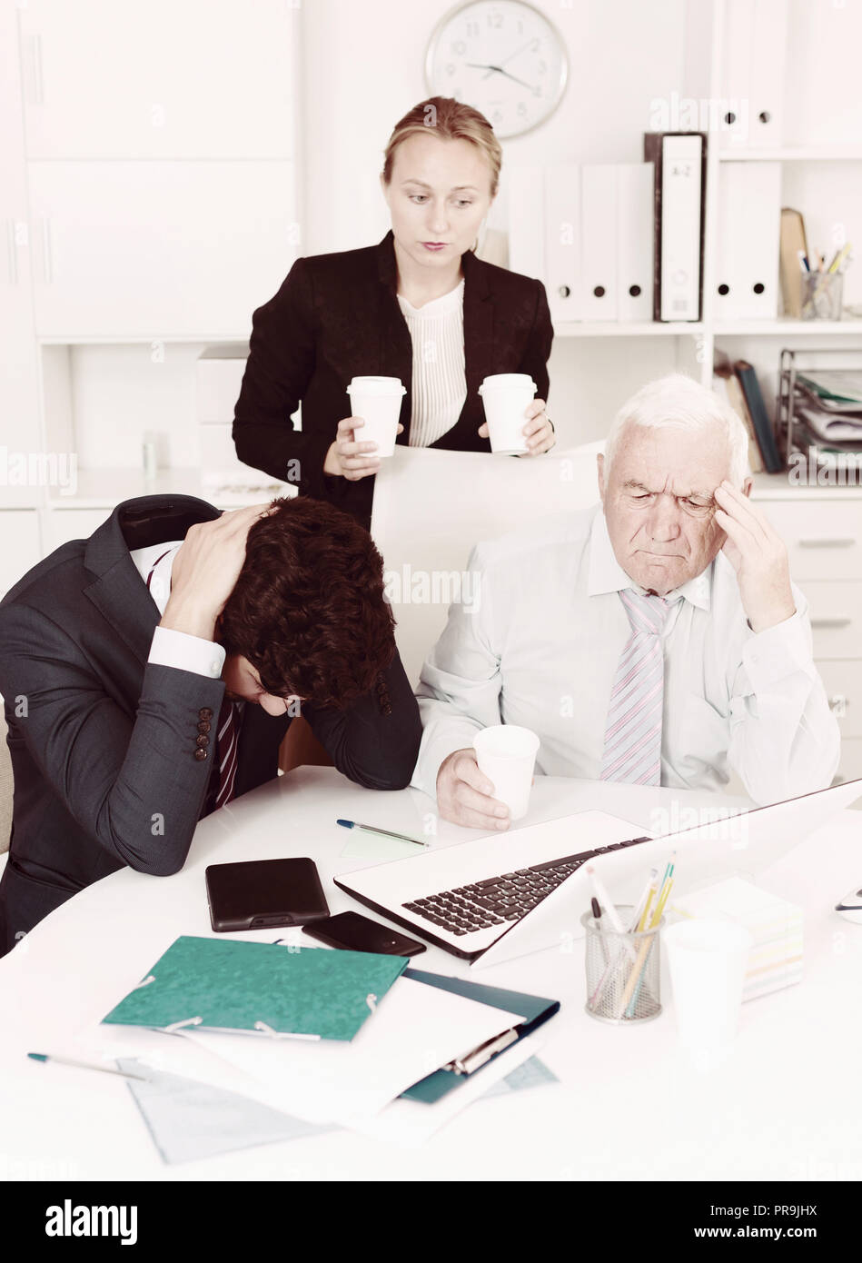 Old man is having complicated issue with reports made by subordinates in office. - Stock Image