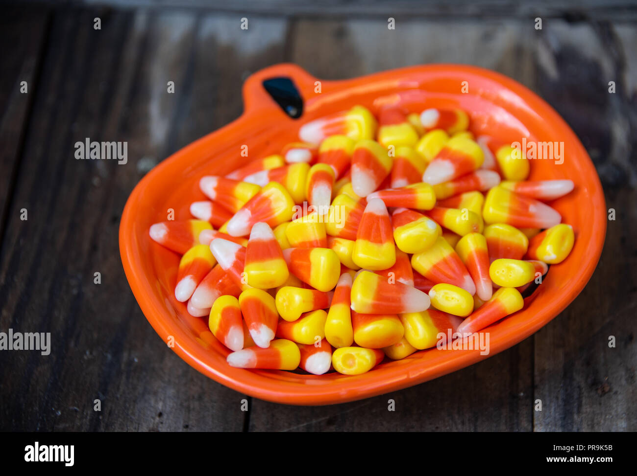 Halloween candy corn in a bright orange pumpkin shaped bowl - Stock Image
