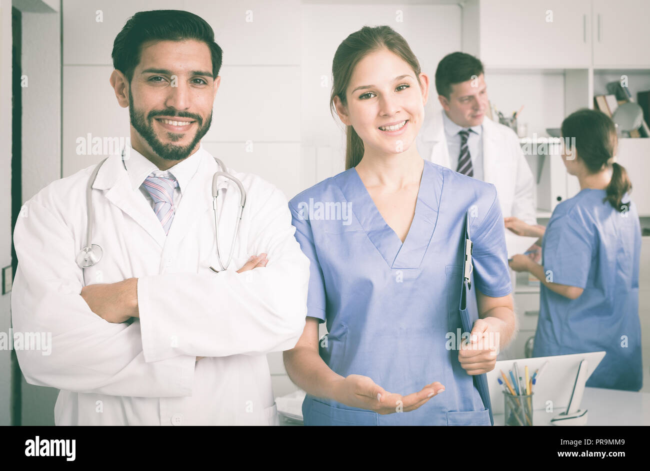 Portrait of young female doctor with male colleague inviting in clinic - Stock Image
