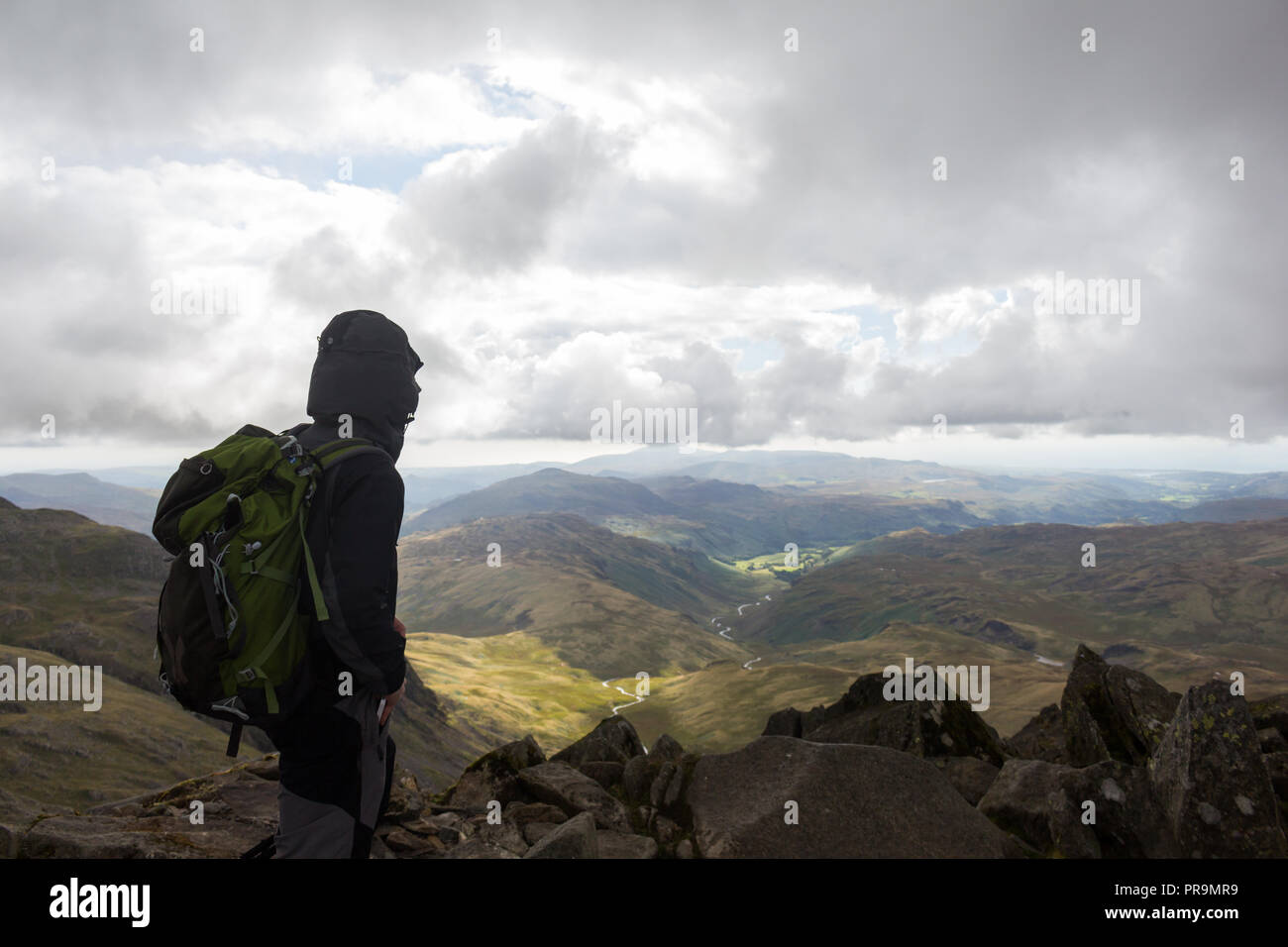 A hillwalker enjoying the view from the summit of Bowfell looking towards Hard Knott on a coudy day in the Lake District, Cumbria, England. - Stock Image