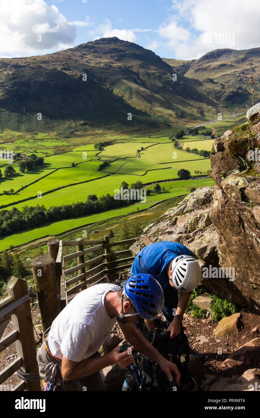 Two climbers gearing up in sunshine in preparation of a climb at Langdale Pikes, Great Langdale, Lake District, Cumbria, England. - Stock Image