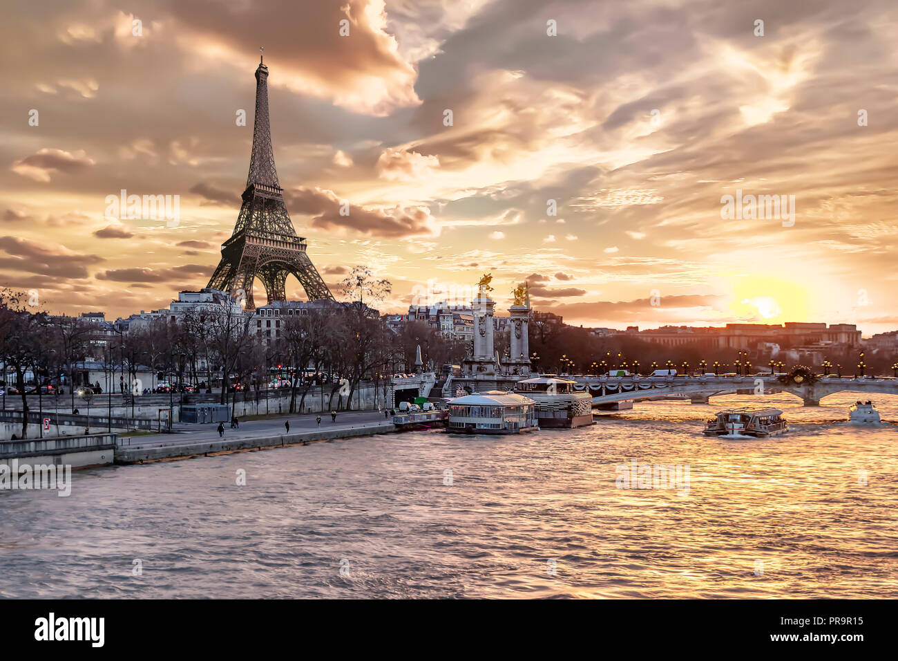Amazing sunset in Paris, with Seine river, Pont Alexandre III and Eiffel tower - Stock Image