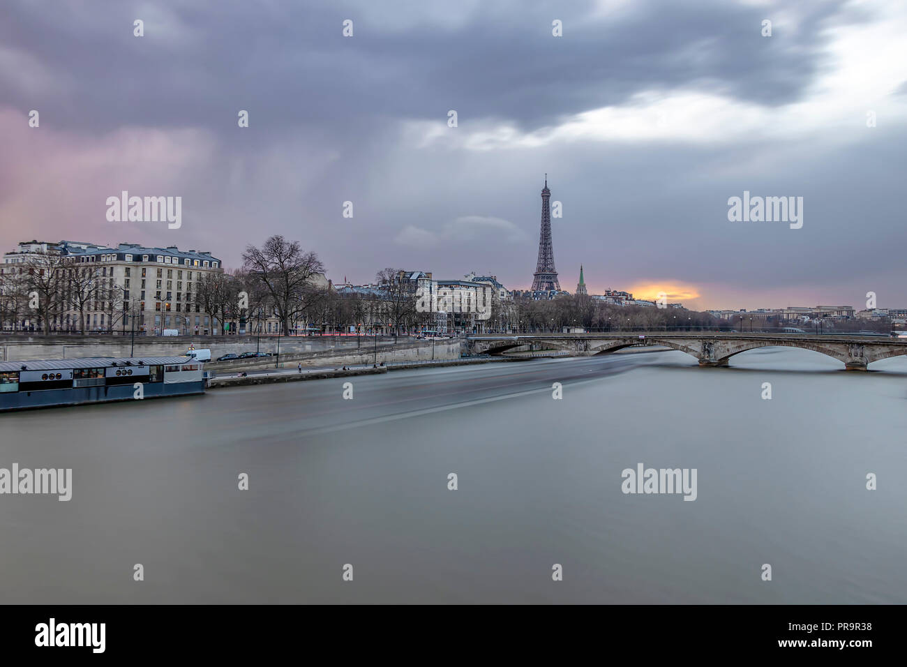 Long exposure photography of sunset in Paris in a cloudy day, with Seine river and Eiffel tower - Stock Image