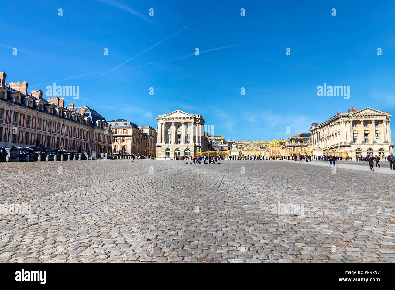 Exterior facade of Versailles Palace with tourists waiting the queue to visit it - Stock Image