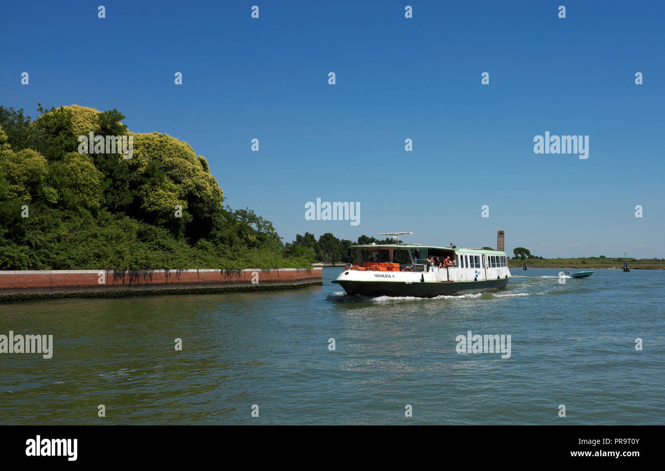Three-quarter view of the front (bow) and side of a water bus (vaporetto) named 'Venezia 4' sailing away from the island of Torcello in Venice, Italy. - Stock Image