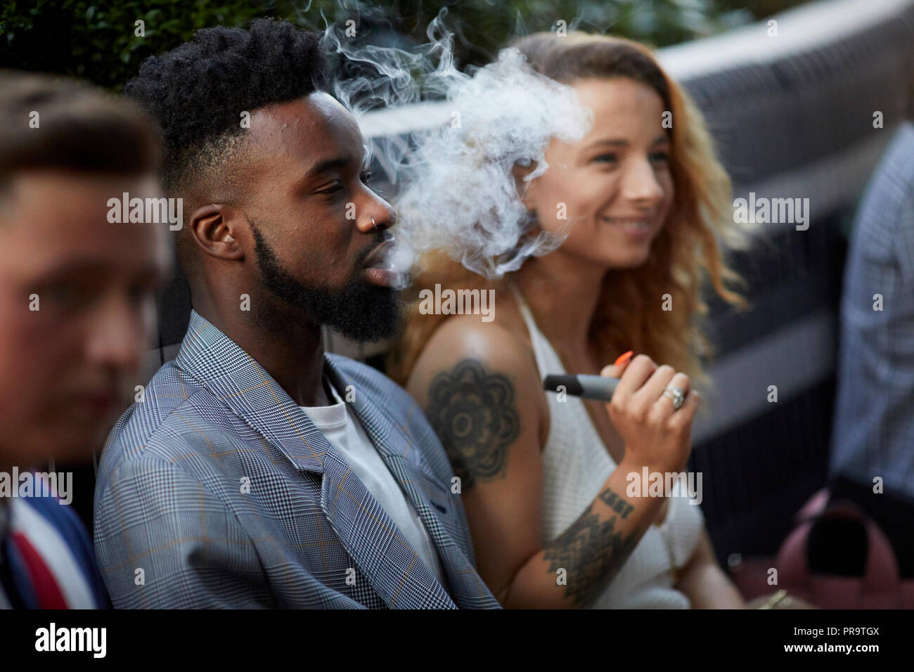 people smoking using vape happing pens in Manchester - Stock Image
