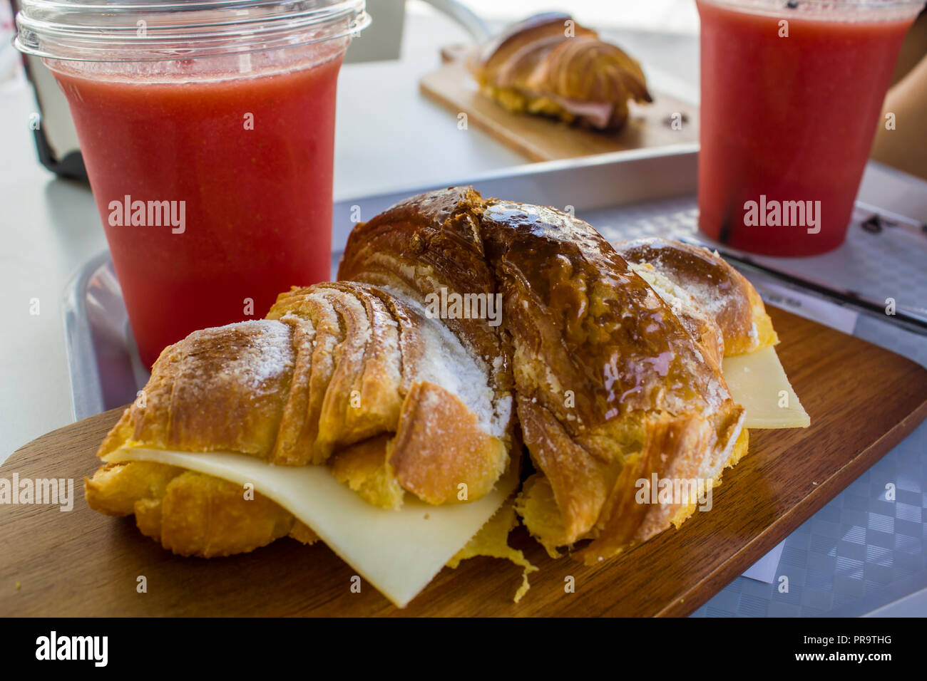 Freshly baked Croissant with cheese and natural watermelon juice on a plastic cup - Stock Image
