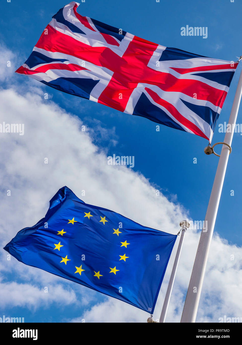 BREXIT UK Union Jack Flag flying high above EU European Flag in a stiff breeze on a sunlit day with blue sky divided by clouds - Stock Image