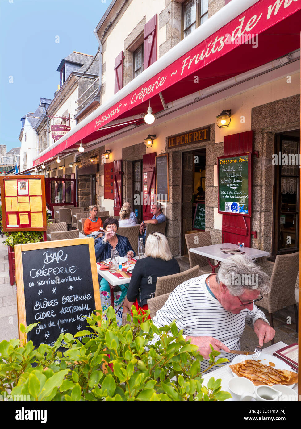 BRITTANY  Blackboard menu Creperie and Bretonne Biers outside  alfresco French restaurant with diner & crepes in foreground Concarneau Bretagne France - Stock Image
