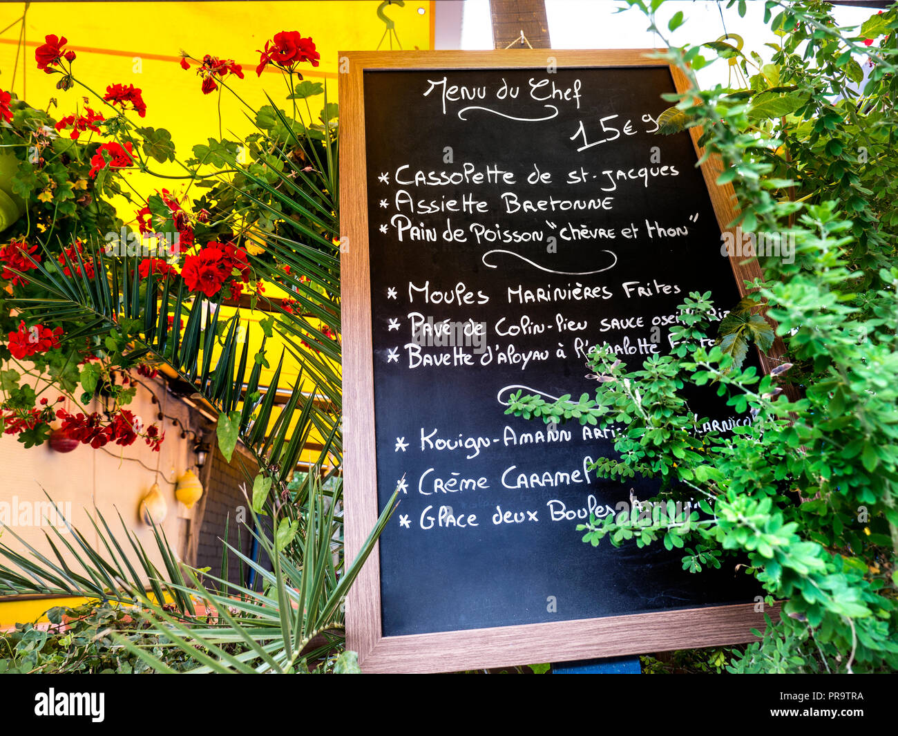 French floral blackboard menu of the day 'Menu du Chef' with local specialities outside typical rustic French restaurant in Concarneau Brittany France - Stock Image