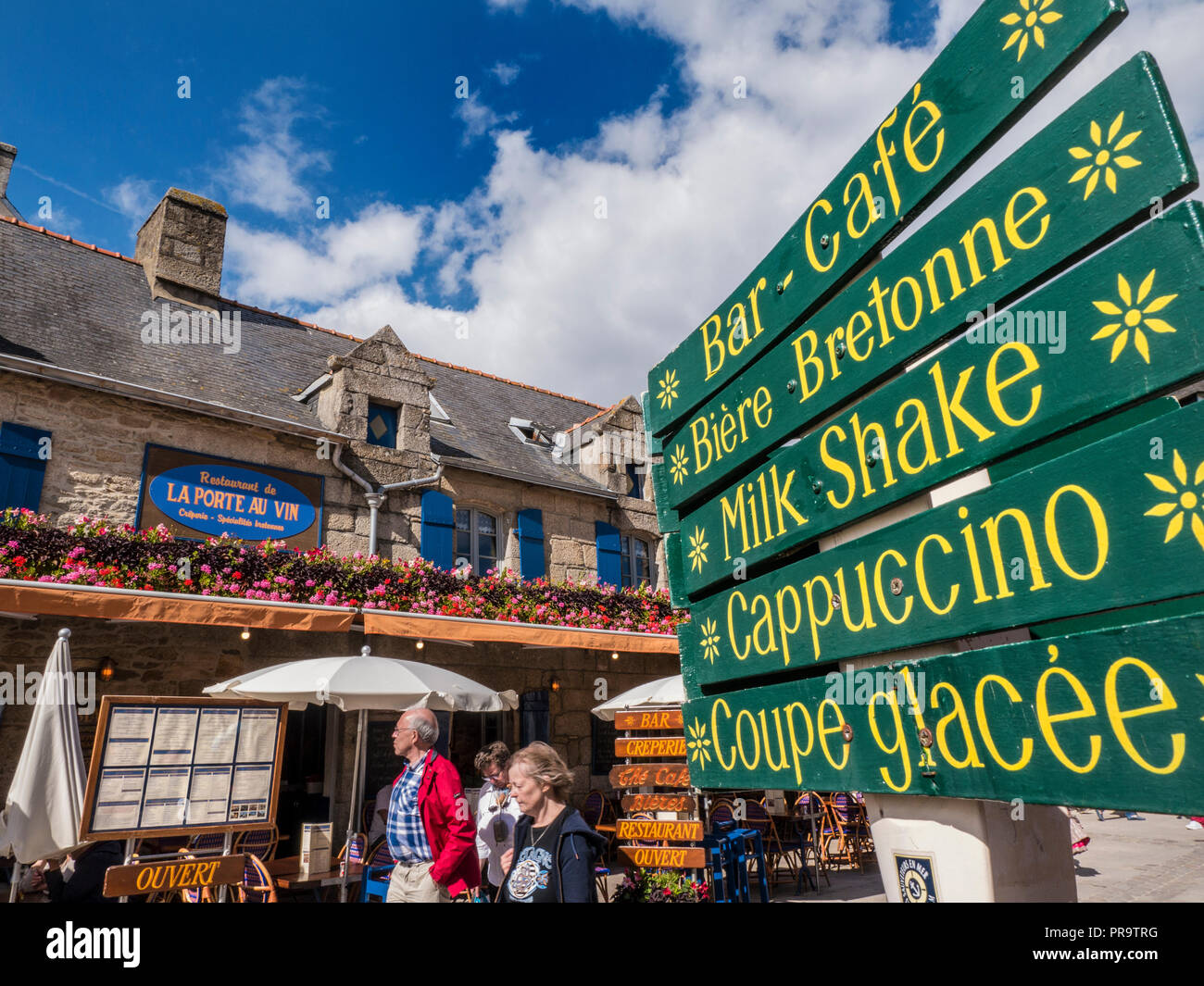 Brittany French alfresco restaurant 'La Port Au Vin' with floral display visitors and café signs Ville Close de Concarneau Bretagne Finistere France - Stock Image