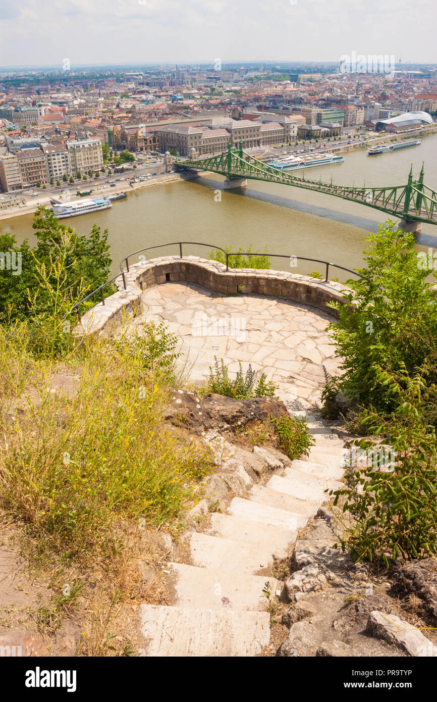 Narrow stairs leading to a viewpoint on Gellert hill with a beautiful panoramic view of Danube river, Liberty bridge and Pest side of Budapest, Hungar - Stock Image