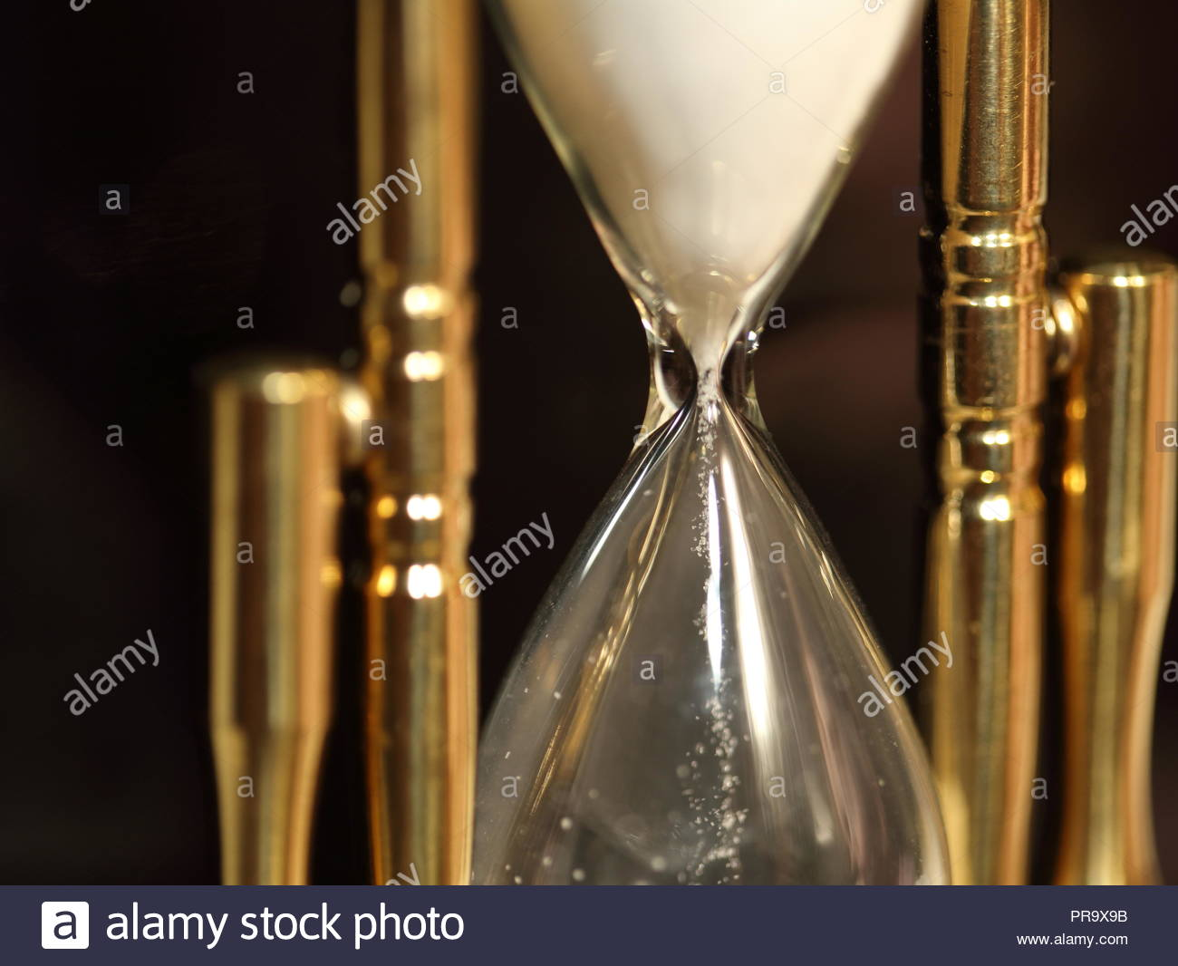 V POINT OF THE HOUR GLASS - Sand slipping through the hour glass. - Stock Image