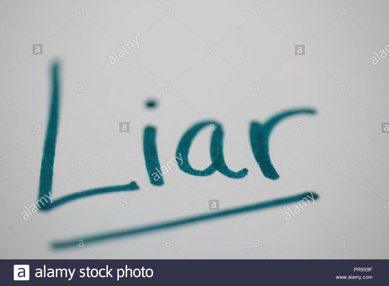 The word Liar written in green marker on white paper. Top and bottom purposefully out of focus for effect. - Stock Image