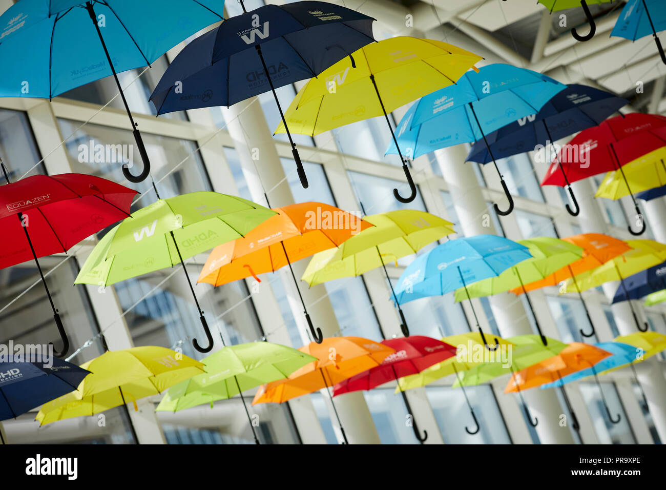 Brightly coloured umbrellas suspended in MediaCityUK Salford Quays to raise awareness of Attention Deficit Hyperactivity Disorder (ADHD) and autism - Stock Image