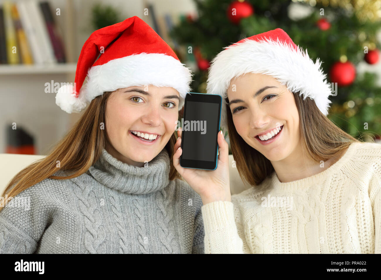Happy girls showing a blank phone screen on christmas sitting on a couch in the living room at home - Stock Image
