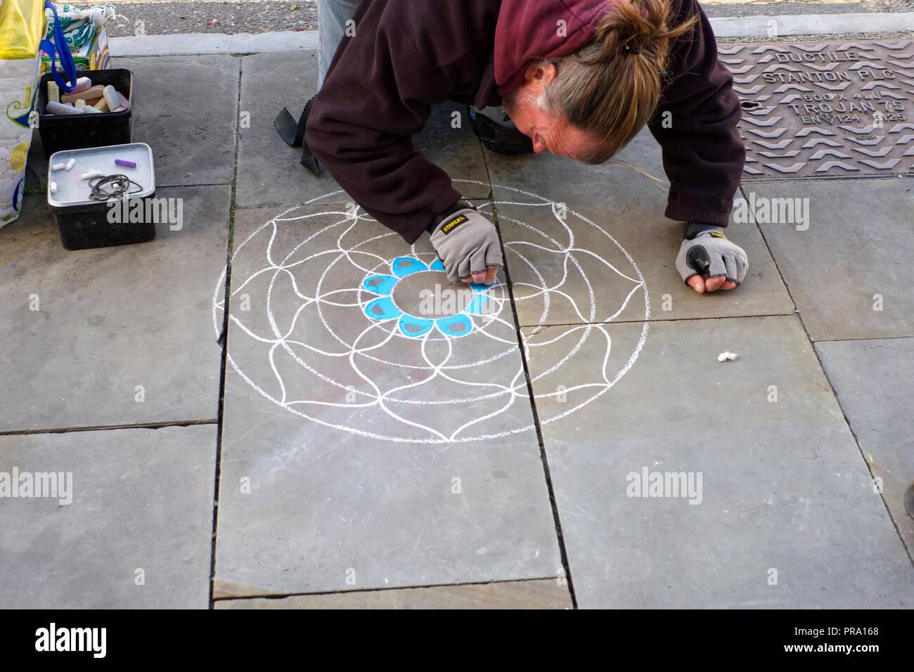 Artist beginning to make his Mandala on the pavement. Glastonbury, Somerset, UK Stock Photo