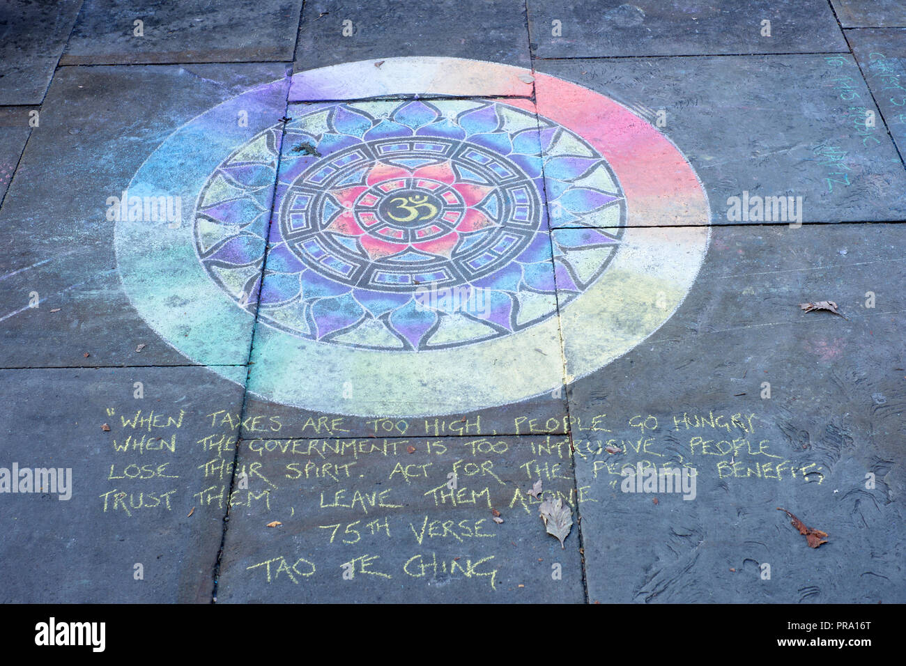 A day old Mandala  with a quote from the 75th verse of the Tao Te Ching which is credited to the 6 century BC sage Laozi. - Stock Image