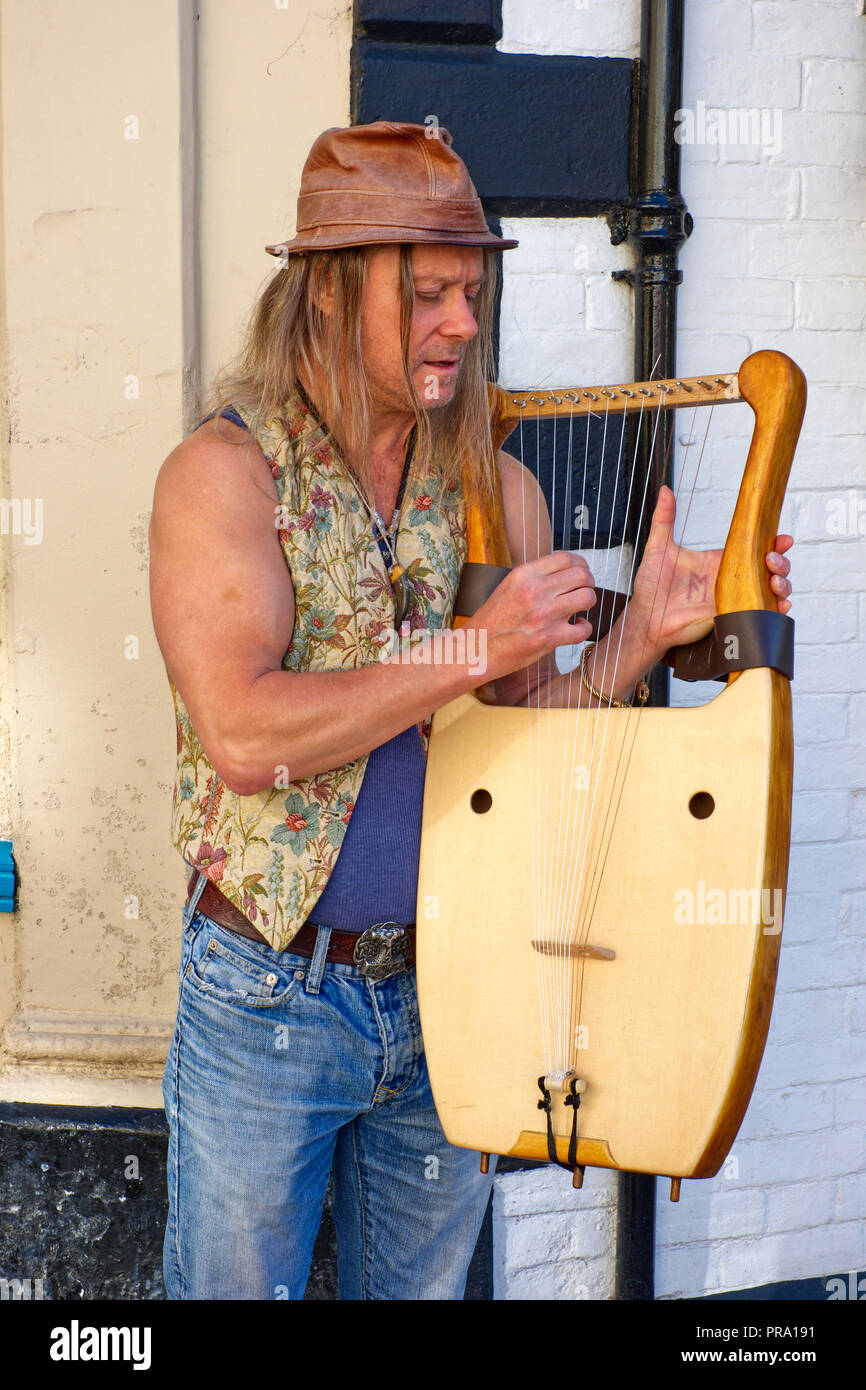 Musician playing a Lyre on the High Street in Glastonbury, Somerset, UK - Stock Image