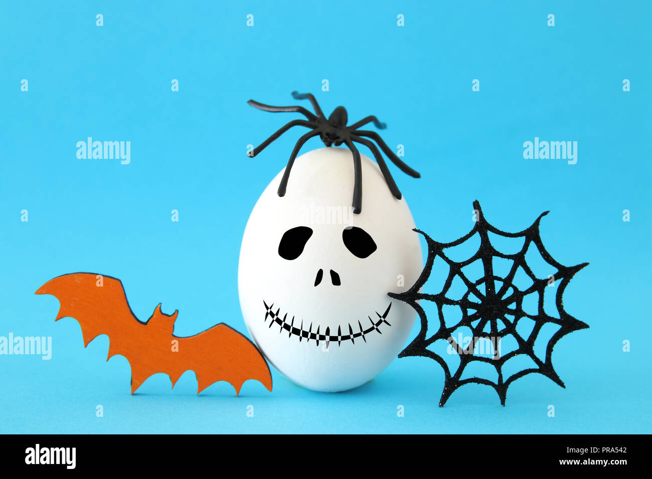 minimal and funny halloween holiday concept. white egg with scary