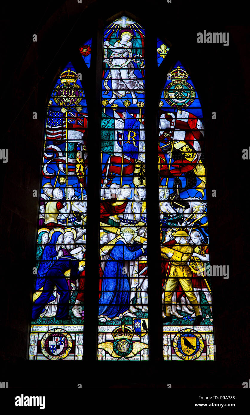 Stained Glass depicting servicemen assiting Jesus with the cross. St George Church Brinsop Herefordshire UK. September 2018. - Stock Image