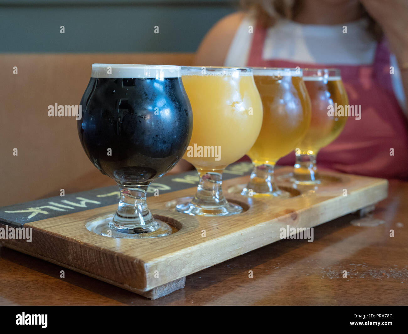 Flight of stout, Amber, IPA beers sitting on wooden paddle  - Stock Image