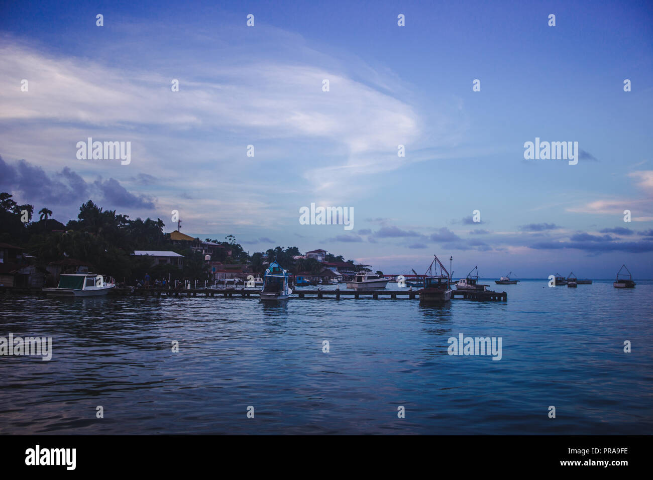 Sunset over boats lined up at the docks of Lívingston, a Garifuna Caribbean town in east Guatemala - Stock Image