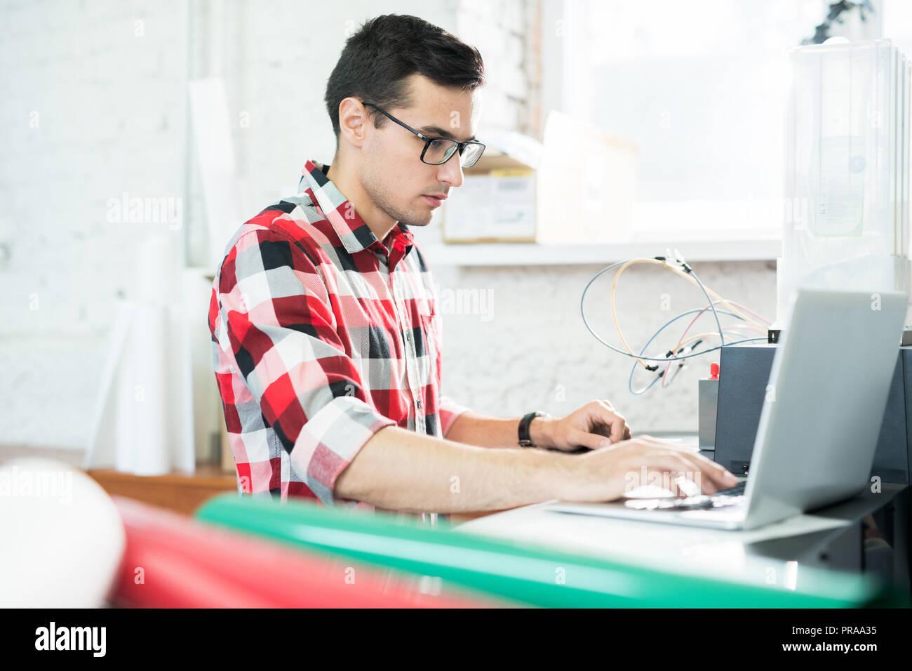 Serious technician testing printer on laptop - Stock Image