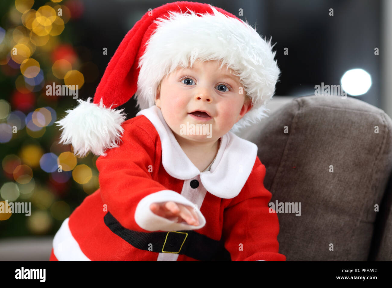 062401bb2 Cute baby wearing santa claus costume on a couch at home in christmas