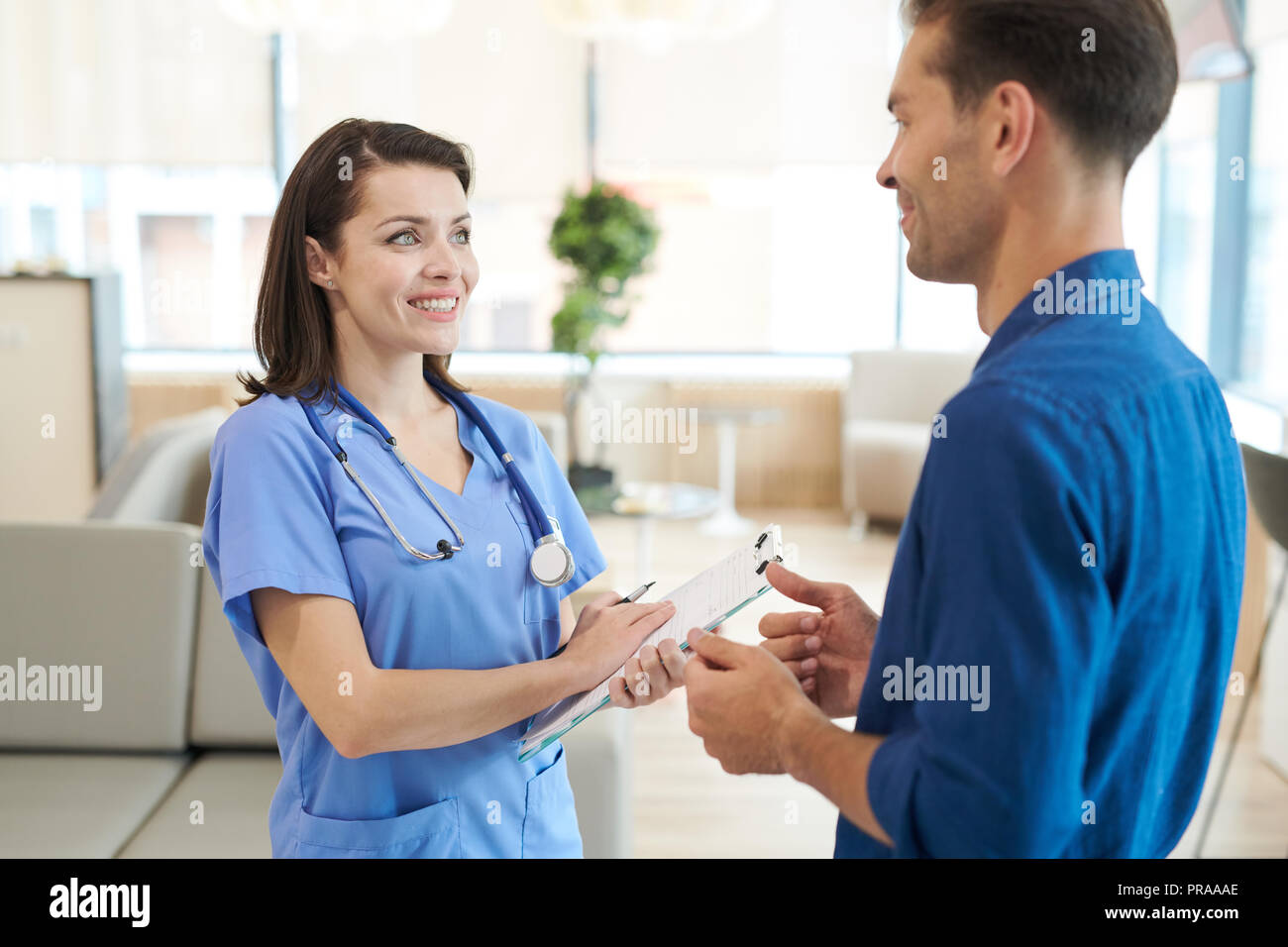 Smiling Nurse Talking to Patient - Stock Image