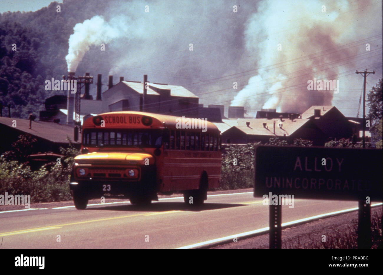 ca. 1998-1999 - school bus driving down road in front of polluting factory (possibly Alloy, West Virginia) - Stock Image