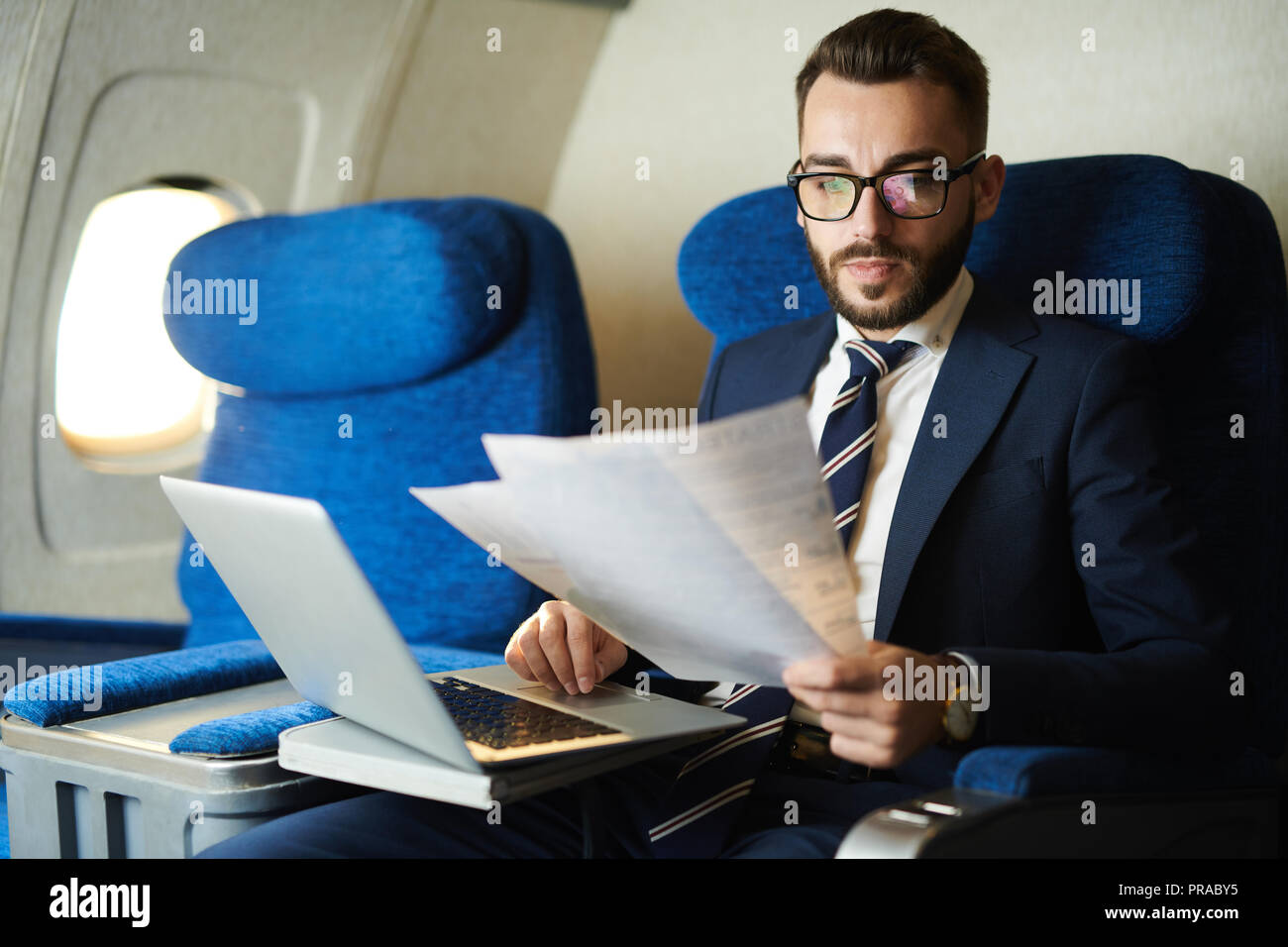 Handsome Business Man Working in Plane - Stock Image