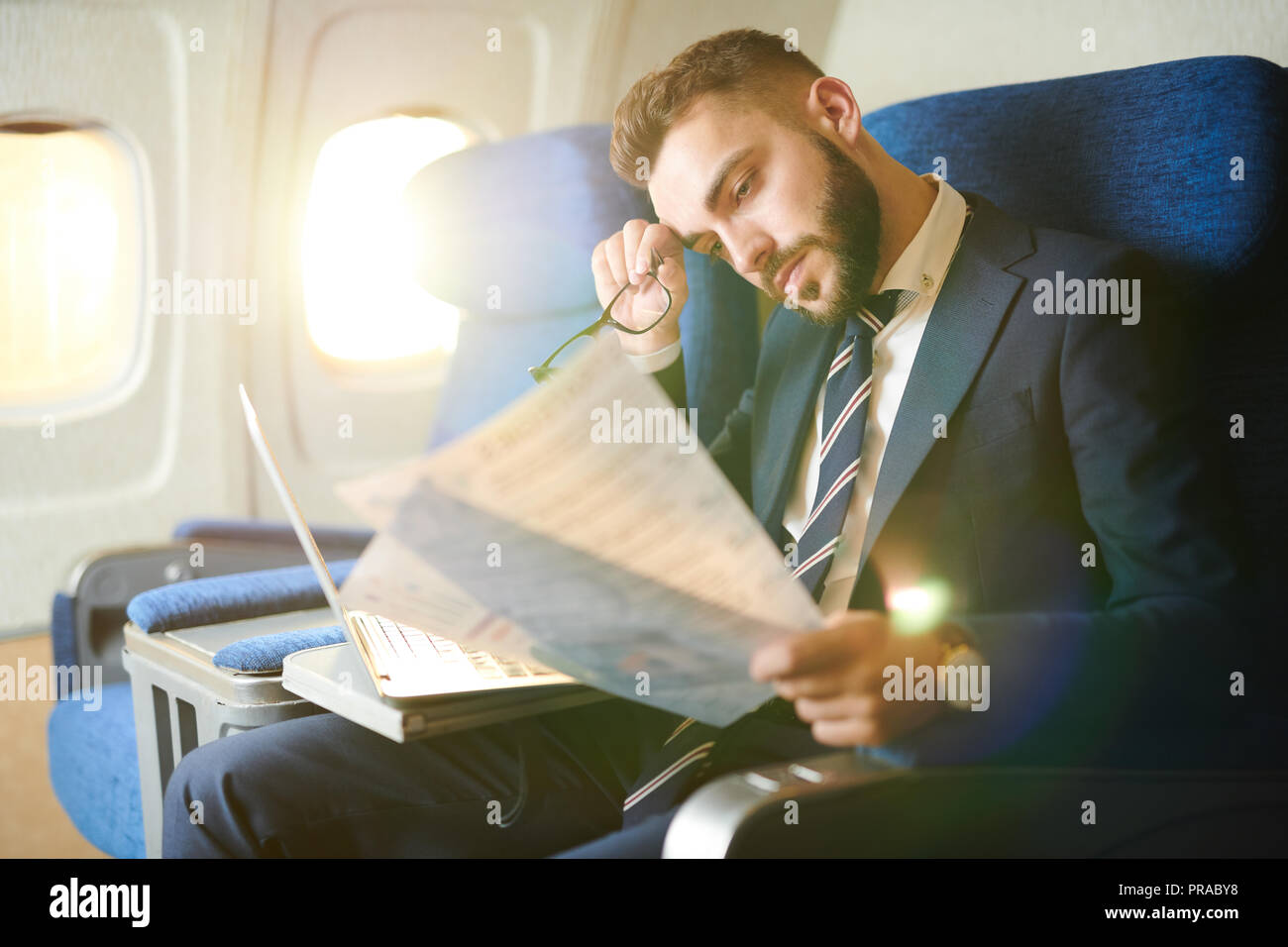 Tired Businessman Working in Plane - Stock Image