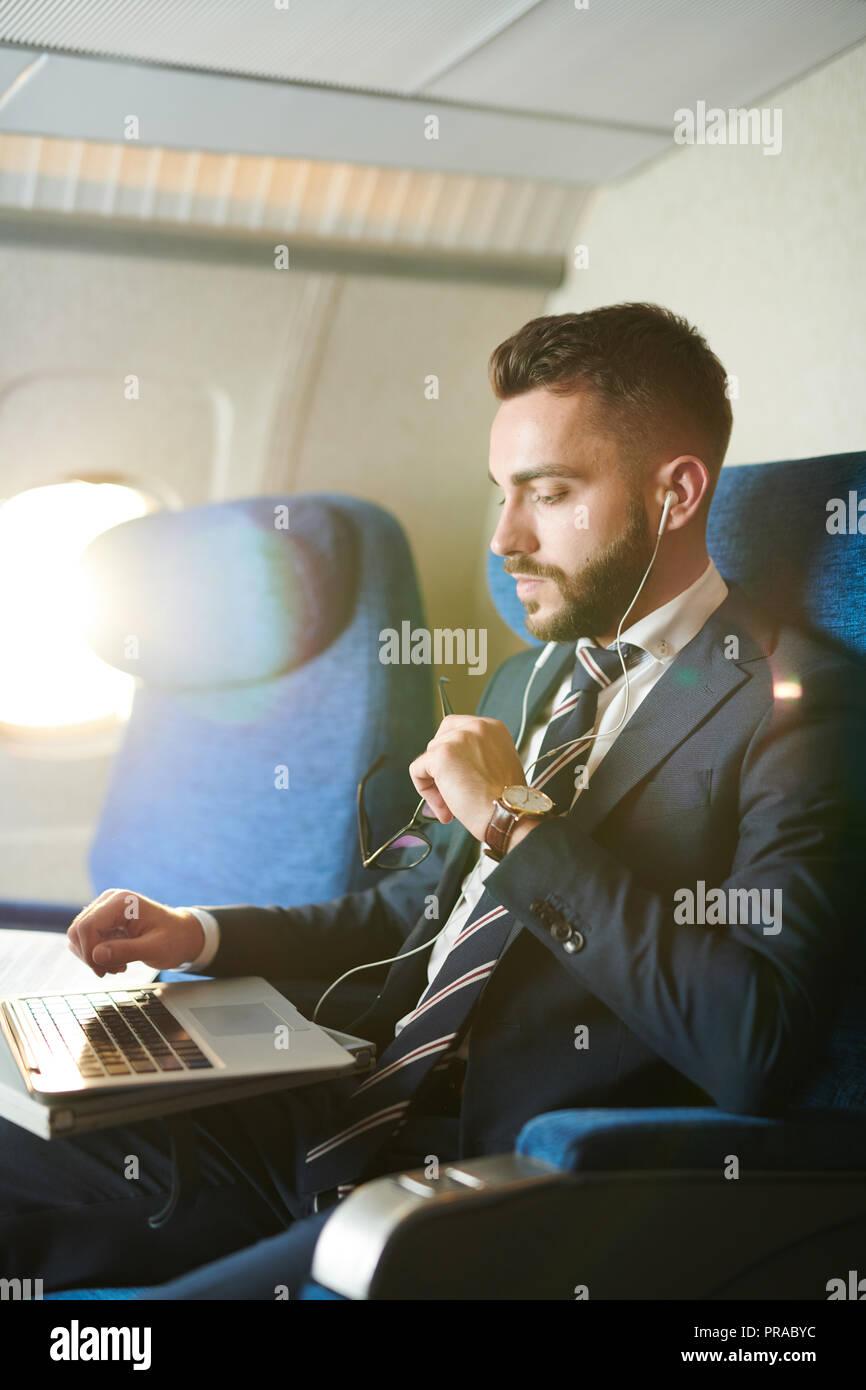 Handsome Businessman in Plane - Stock Image