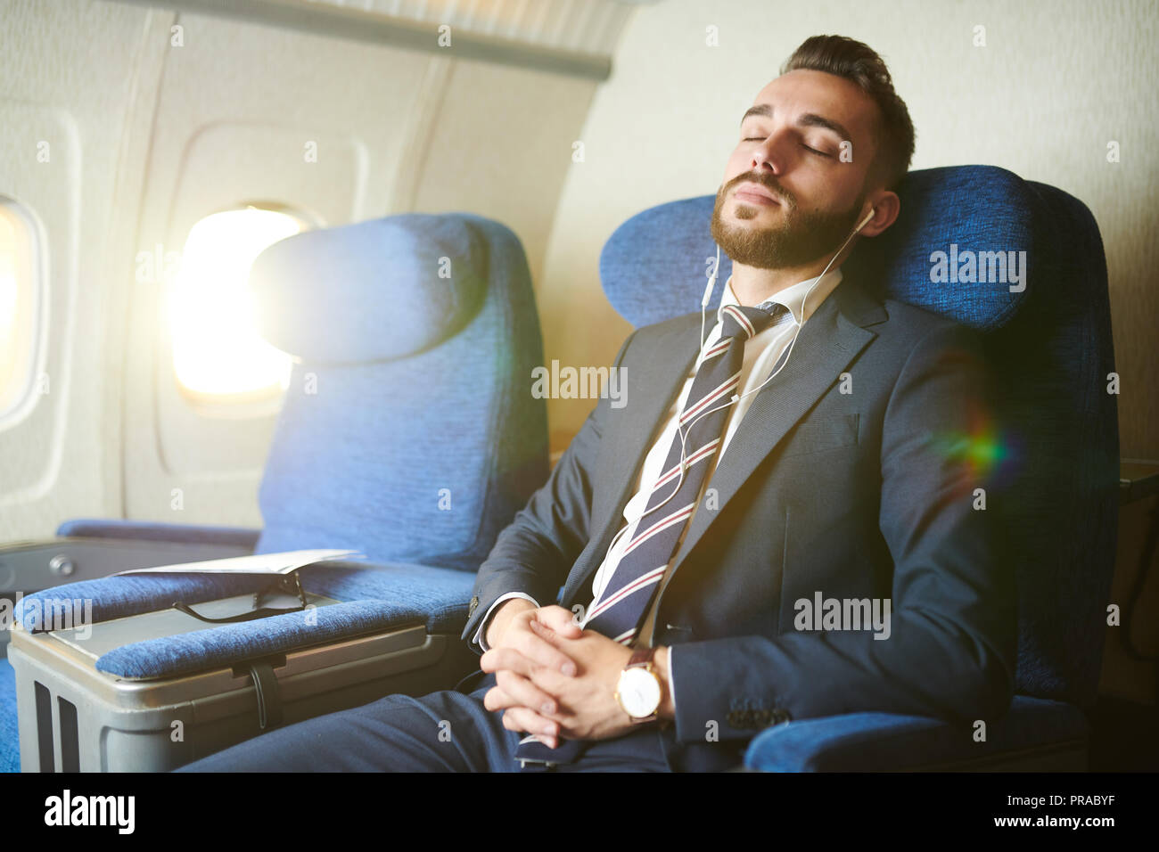 Handsome Businessman Sleeping in Plane - Stock Image