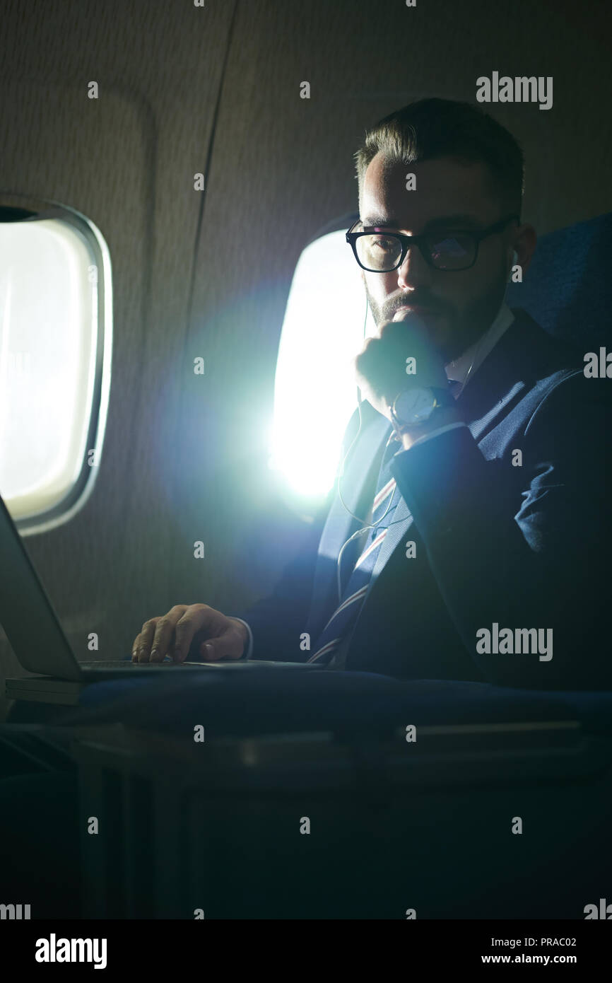 Pensive Businessman in Plane - Stock Image