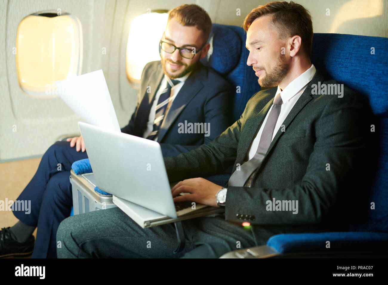 Unrecognizable Businessman in Plane - Stock Image