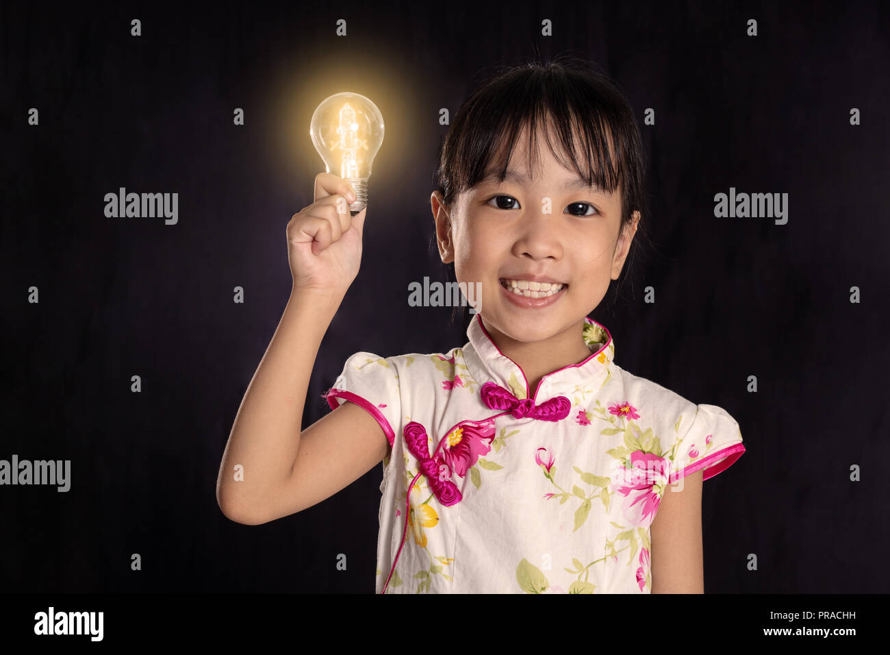 Asian chinese little girl holding a light bulb in isolated black background - Stock Image
